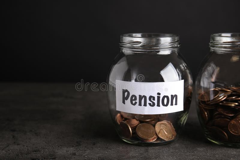 Glass jars with coins and label PENSION on dark table royalty free stock images