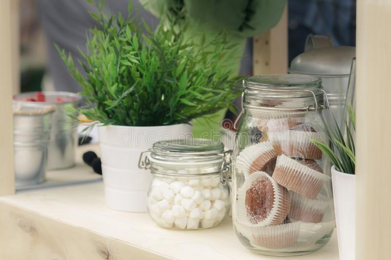 Glass jars with cookies and muffins, green seedlings in metal decorative pails.  stock photography