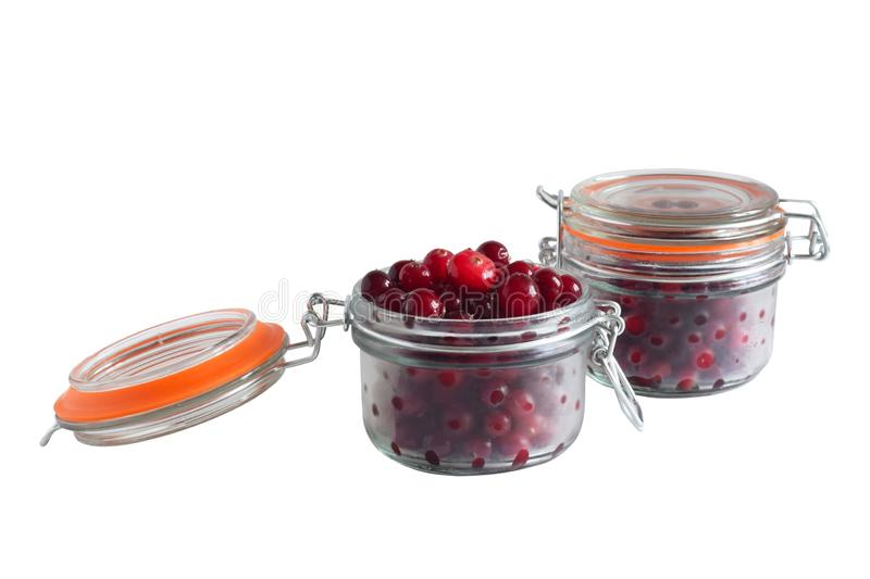 Glass jars with cranberries on white background royalty free stock image