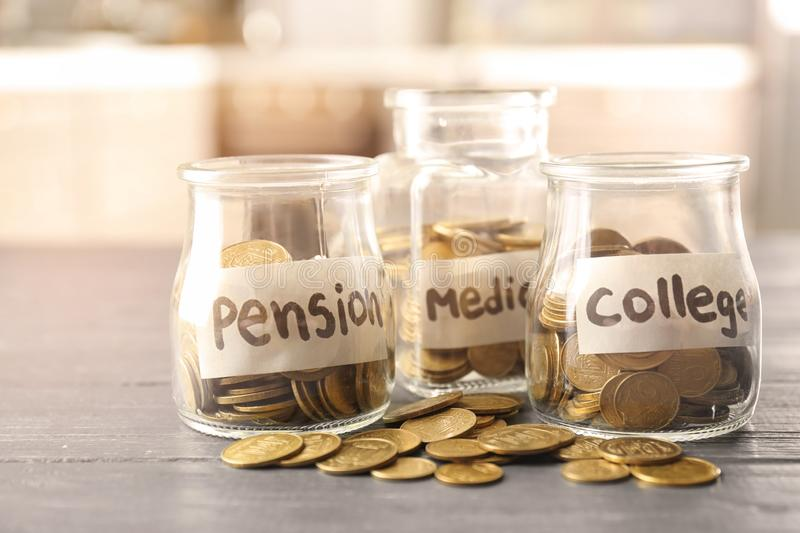 Glass jars for different needs full of coins on wooden table stock photography