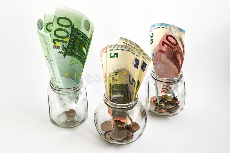 Glass jars filled with coins and Euro bills, savings inside glass jar, money isolated on white. Glass jars filled with coins and Euro bills, savings, money, ank stock photography