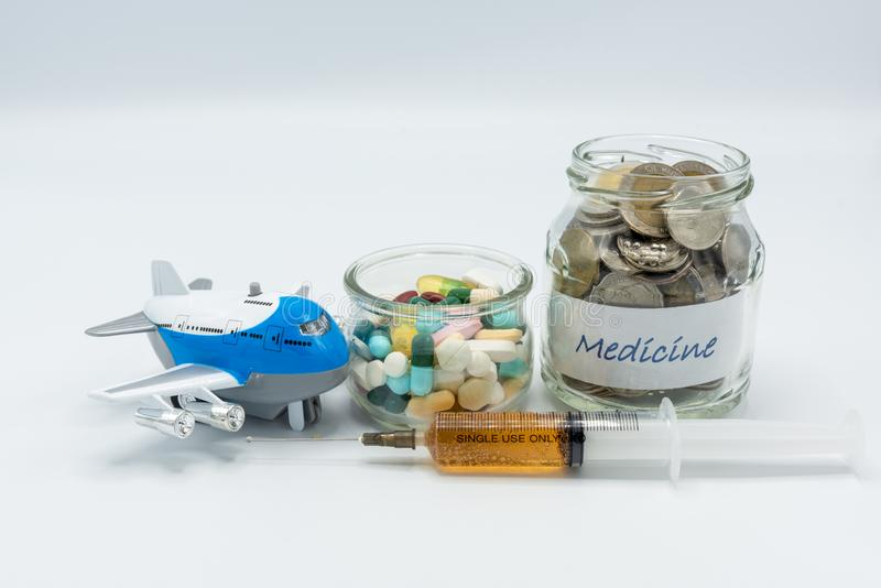 Glass jars filled with coins and medicine together with toy airplane and syringe filled with yellow solution royalty free stock image