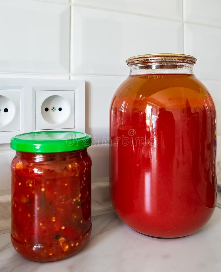 Glass jars with juice and lecho. Stand on the table stock photography