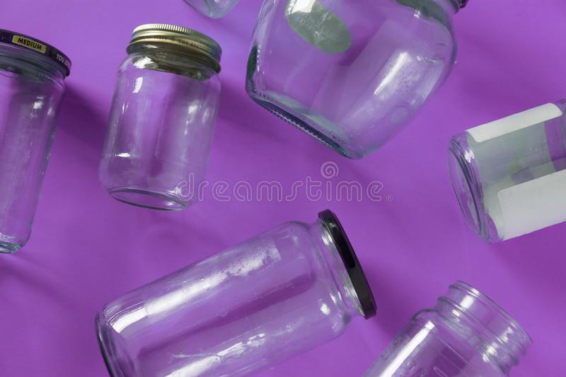 Glass jars with lids, purple background, top view flat lay recycling concept royalty free stock images