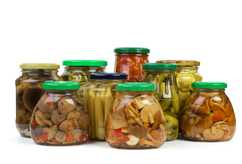 Glass jars with marinated vegetables and mushrooms royalty free stock images