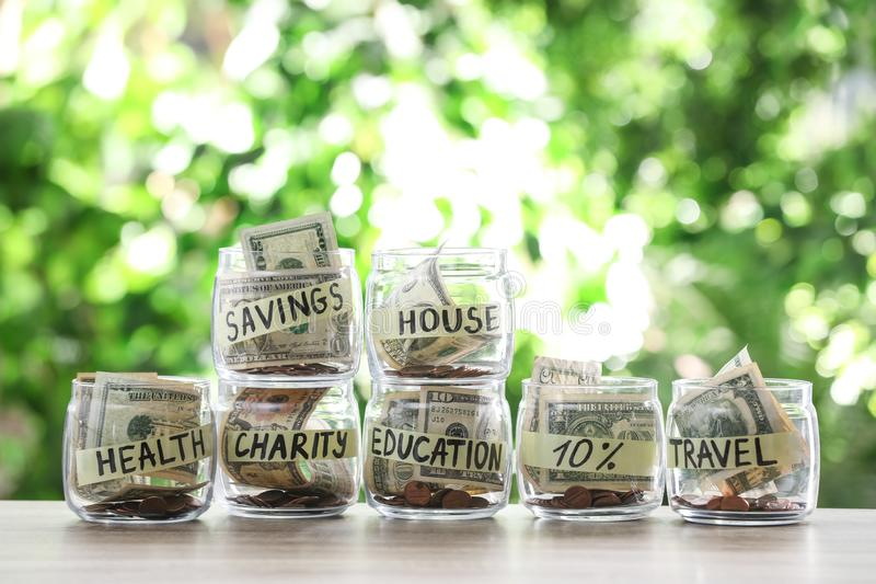 Glass jars with money for different needs on table royalty free stock photo