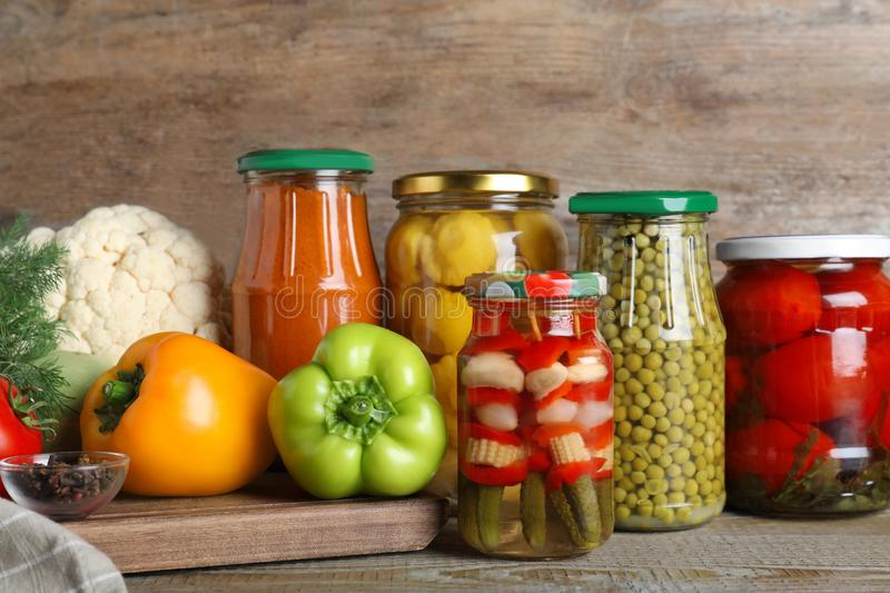 Glass jars with pickled vegetables on wooden table stock image