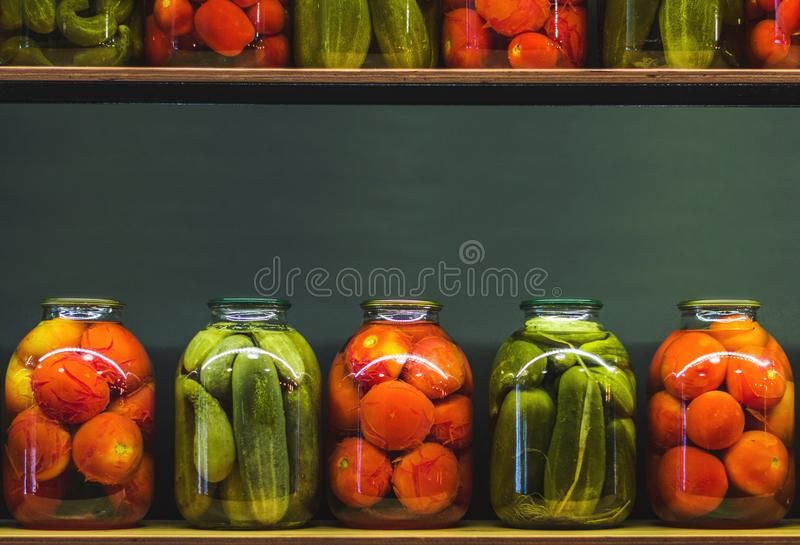 Glass jars with pickles. Jars with tomatoes and pickles. Picture with copy space royalty free stock photo