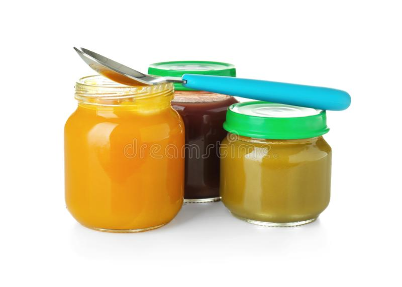 Glass jars and spoon with healthy baby food on white background royalty free stock photography