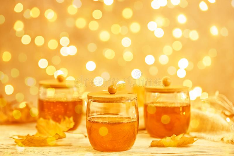 Glass jars with sweet honey on table against blurred lights royalty free stock images