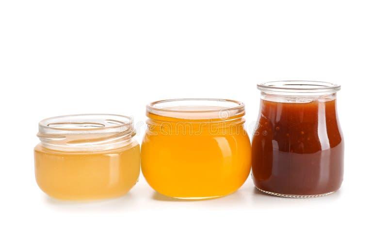 Glass jars with tasty honey on white background royalty free stock photo