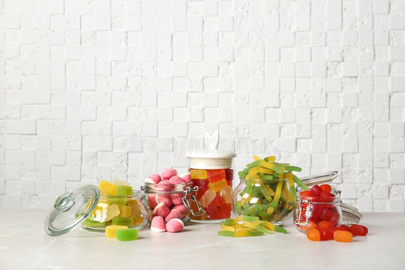 Glass jars with tasty jelly candies on table against white wall stock photos