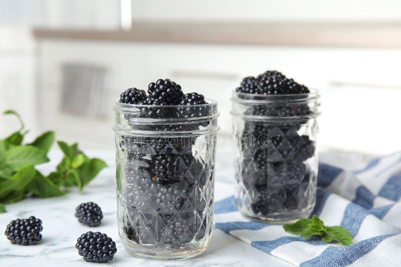 Glass jars of tasty ripe blackberries on table royalty free stock image