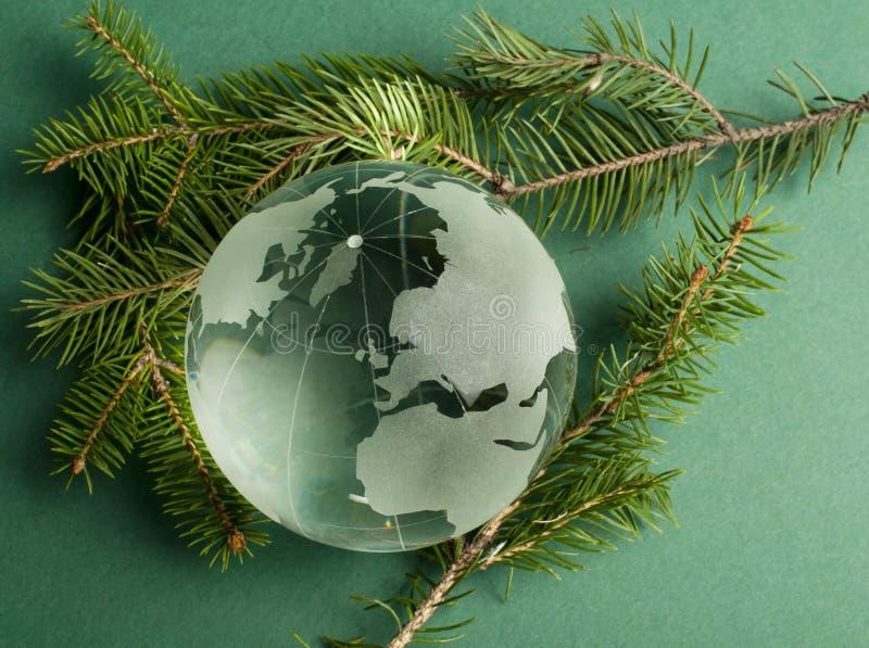 Glass jordklot på gröna granfilialer royaltyfri fotografi