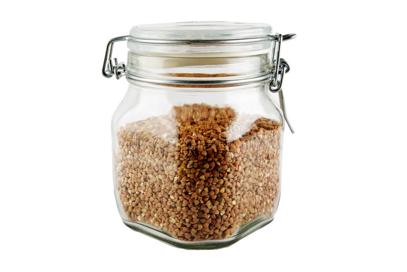 Glass jug with buckwheat royalty free stock photo