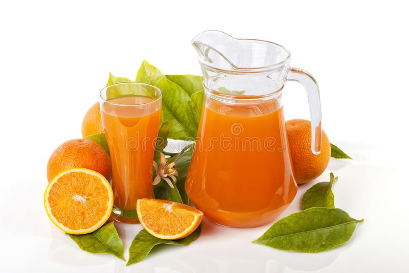 A glass jug and glass filled with orange juice isolated stock image