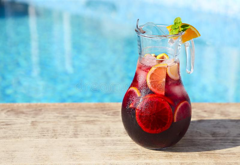 Glass jug of iced sangria with strawberry, orange, apple and lemon royalty free stock images