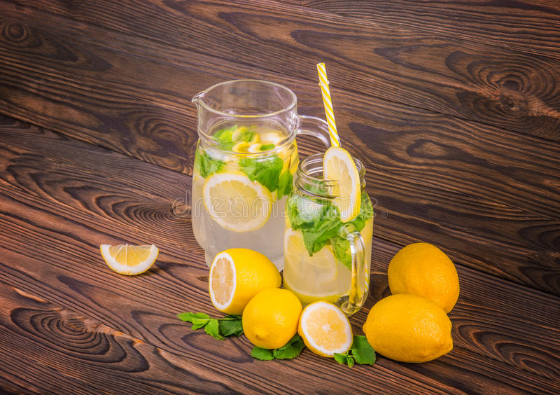 A glass jug with lemon juice, a glass with long yellow straw and lemons stand on a wooden, table isolated on a white background. royalty free stock image