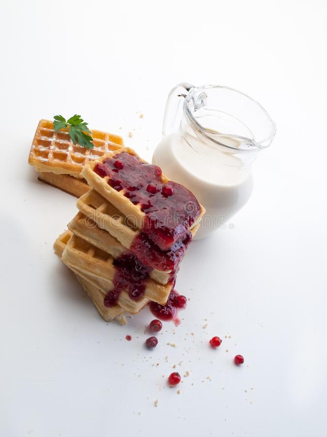 A glass jug with milk next to waffles and currant jam. A glass jug with milk next to waffles and gooseberry jam seen overhead on a white background royalty free stock image