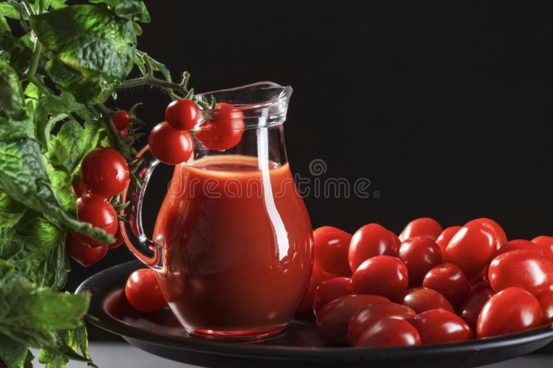 Glass jug with tomato juice stands covered with cherry tomatoes next to a natural tomato bush, conceptual image royalty free stock photography