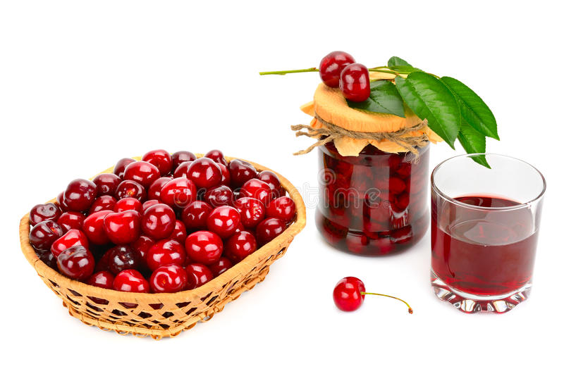 Glass of juice, basket of cherries and jar of jam royalty free stock photo