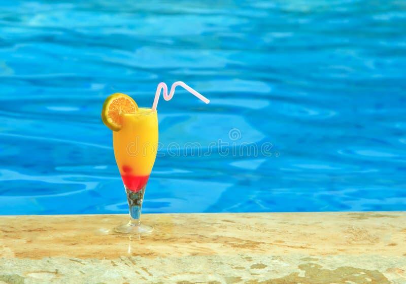 Glass of juice is on edge of pool stock image