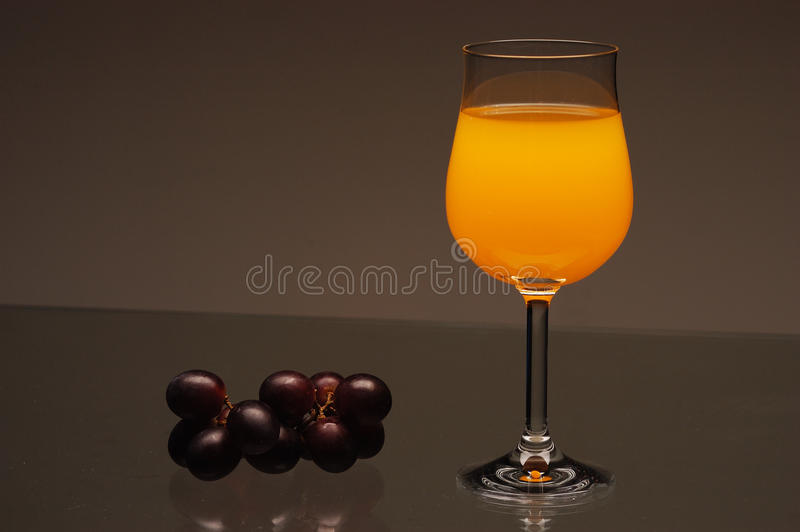 Glass of juice with grapes. Black grapes and a glass of orange juice on a glass table. Grey background stock photos