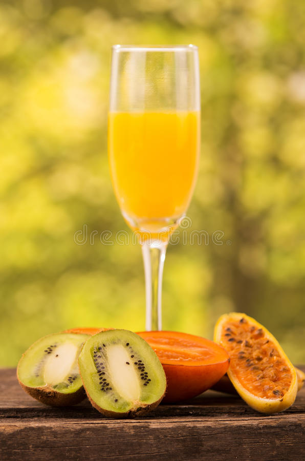 Glass of juice with kiwi, tree tomato and banana. Glass of juice with slices of kiwi, tree tomato and banana passionfruit on a wooden table over a forest royalty free stock image