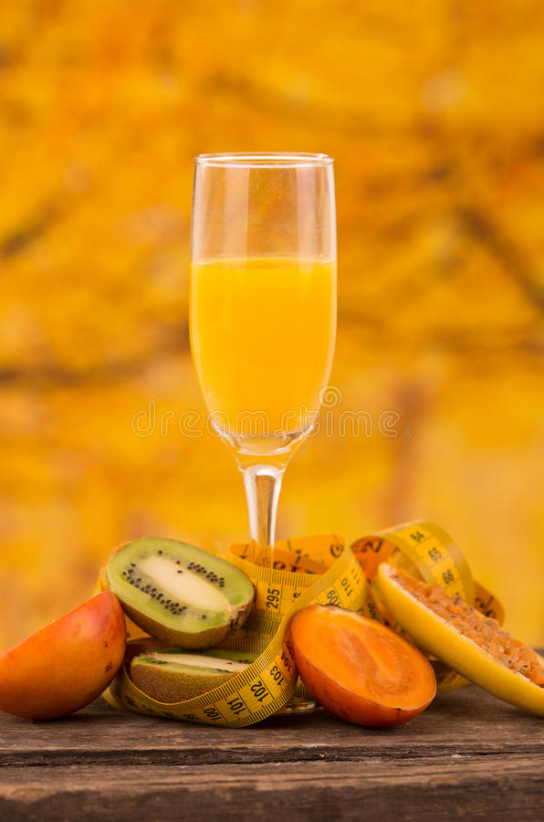 Glass of juice with kiwi, tree tomato and banana. Glass of juice with slices of kiwi, tree tomato and banana passionfruit on a wooden table over a yellow royalty free stock photo