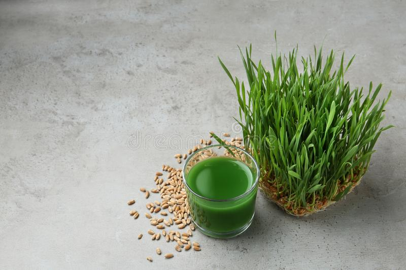 Glass of juice, sprouted wheat grass and grains on grey stone background royalty free stock photography