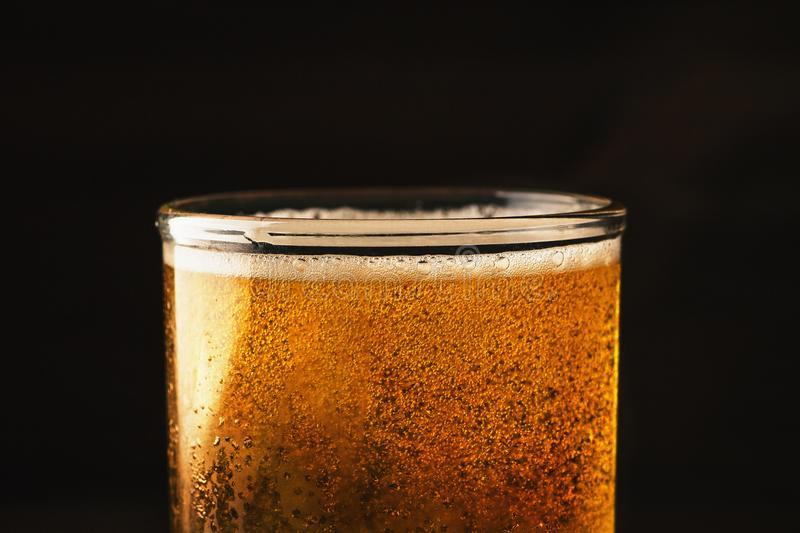 Glass of just poured beer with little foam and bubbles, macro shot stock photos