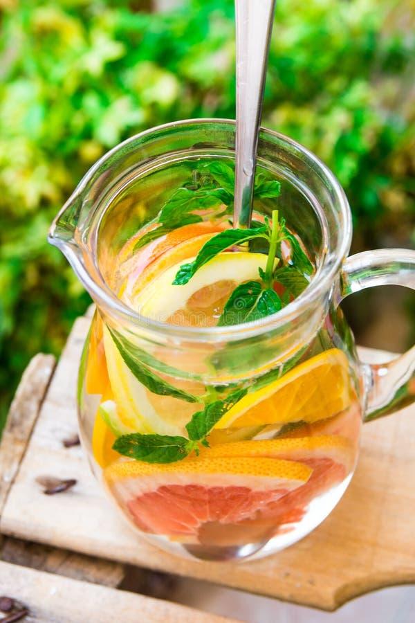 Glass kanna med detox ingett citrust vatten med grapefrukter, apelsiner, limefrukter, citroner, ny mintkaramell, träträdgårds- fr arkivbild