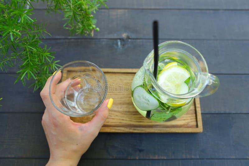 Glass karaff och exponeringsglas fasetterad kopp som rymms i handen s arkivbild