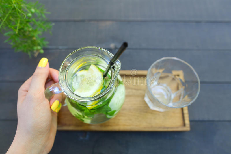 Glass karaff som rymms i hand och exponeringsglas fasetterad koppställning royaltyfri fotografi