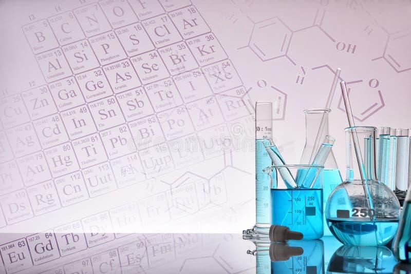 Glass kemiska behållare med blå flytande och bakgrund med r royaltyfria foton