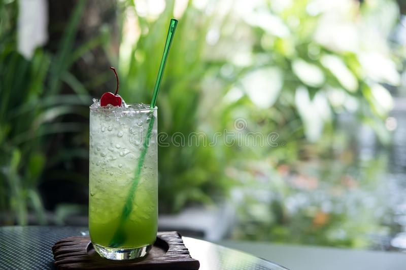 A glass of kiwi italian soda on a wooden saucer in cafe royalty free stock photography