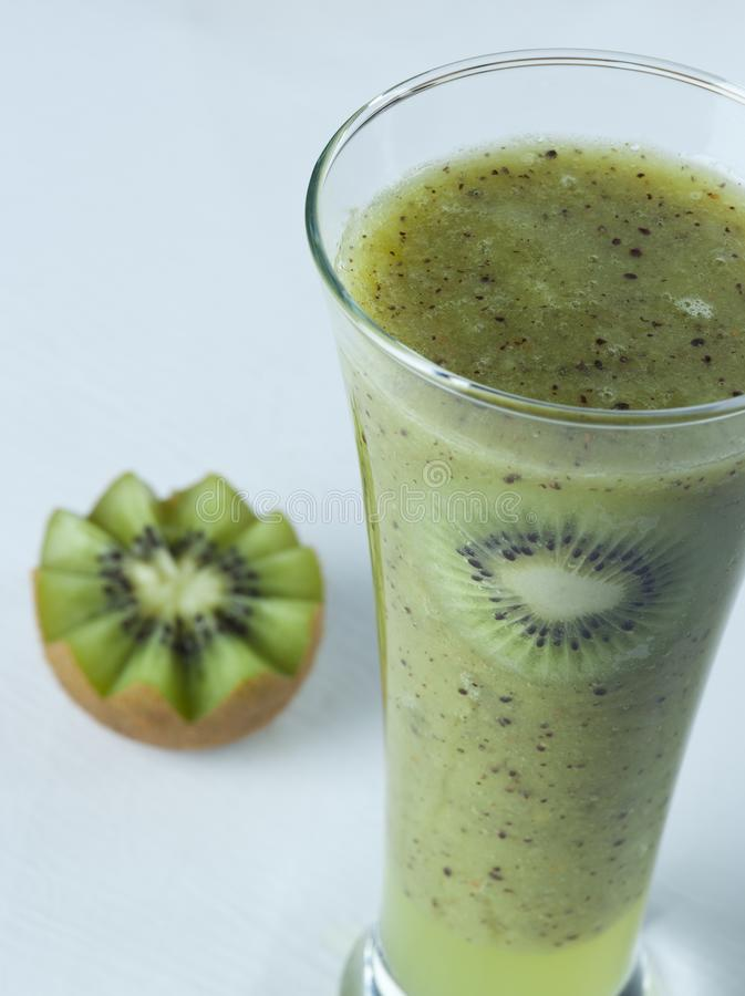 A glass of kiwi Juice with slices and fruits royalty free stock image
