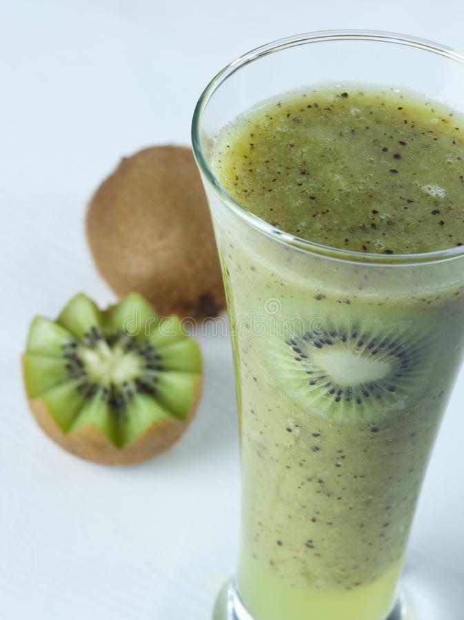 A glass of kiwi Juice with slices and fruits stock photography