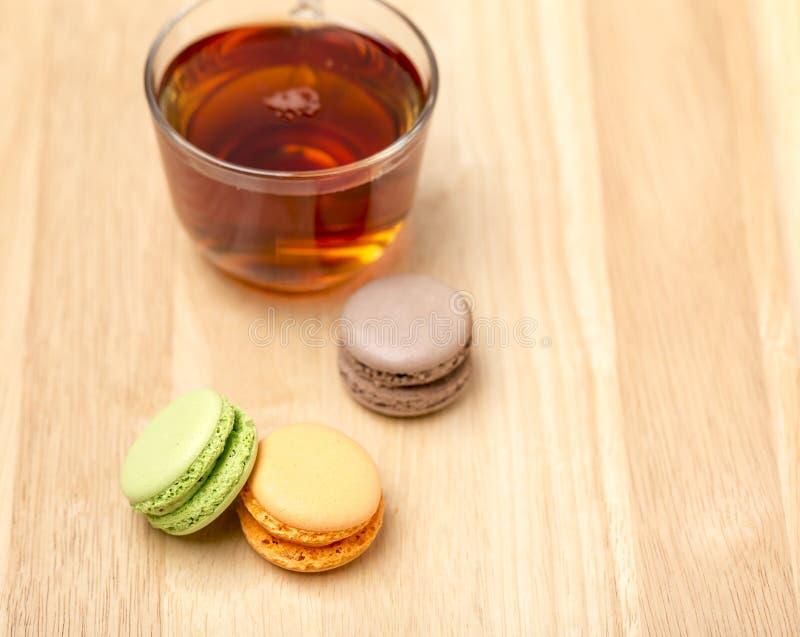 Glass kopp av svart te och färgrika macarons royaltyfria bilder