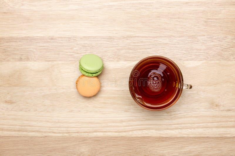 Glass kopp av svart te och färgrika makron för stad arkivbild