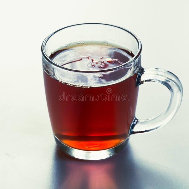 Glass kopp av varmt svart te på vit Slapp fokus close upp royaltyfri fotografi