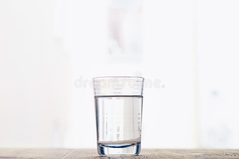 Glass kopp med vatten på en bakgrund av fönstret royaltyfri foto