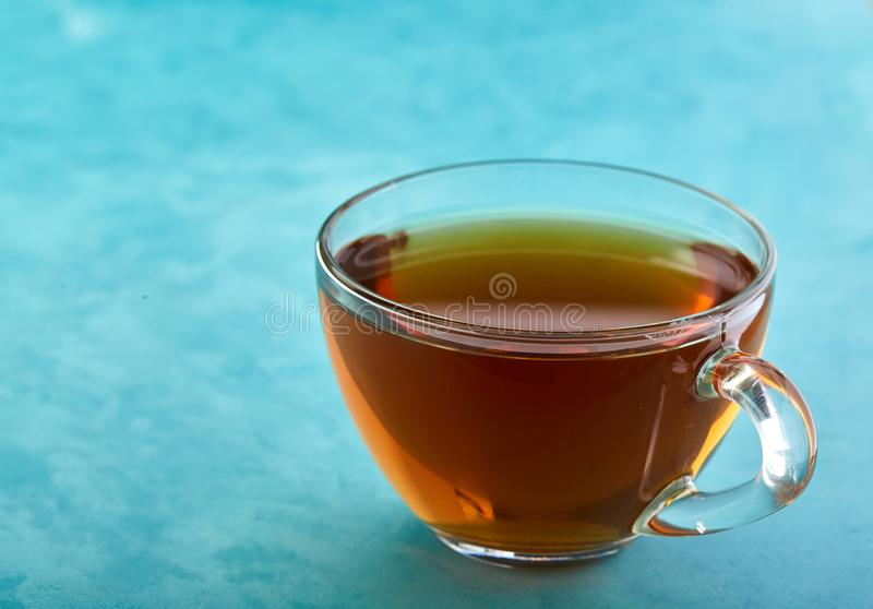 Glass kopp te- och chokladkakanärbild på blå bakgrund arkivbild