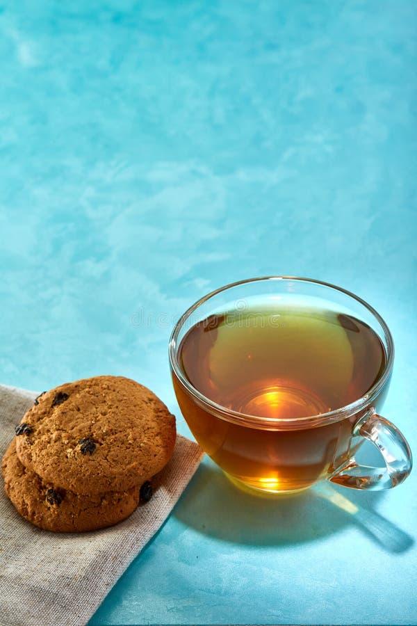 Glass kopp te- och chokladkakanärbild på blå bakgrund royaltyfria foton