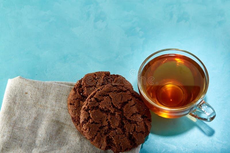 Glass kopp te- och chokladkakanärbild på blå bakgrund royaltyfri fotografi