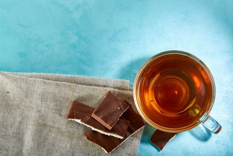 Glass kopp te- och chokladnärbild på blå bakgrund arkivfoton