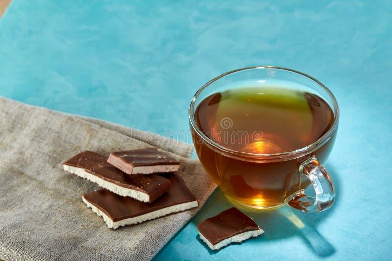 Glass kopp te- och chokladnärbild på blå bakgrund arkivfoto