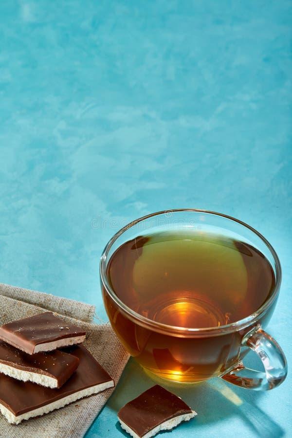 Glass kopp te- och chokladnärbild på blå bakgrund, lodlinje fotografering för bildbyråer