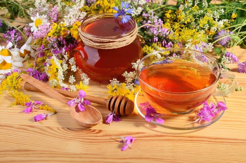 Glass kruka av honung med te arkivfoton