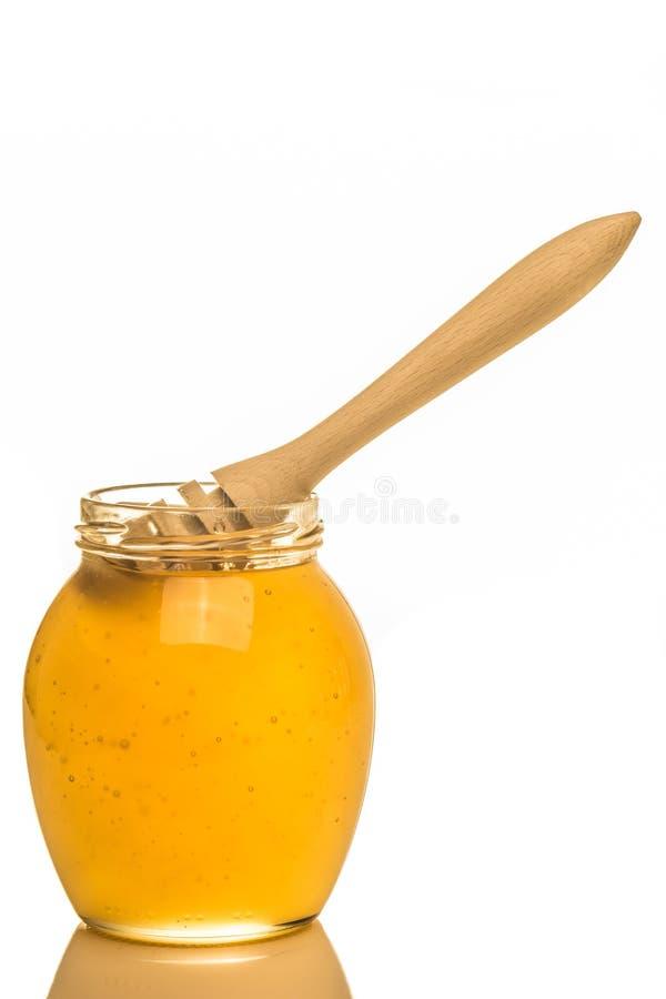 Glass krus av honung med trädrizzler som isoleras på vit backgr arkivfoton